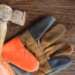 Old Hammer and leather gloves on wood background — Stock Photo