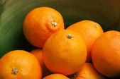 Some oranges fruits in a green bowl — Stock Photo
