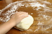 Child's hands kneading bread dough — Stock Photo
