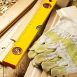 Foto Stock: Carpenters level, nails and work gloves are on wooden planks