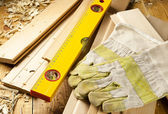 Carpenters level, nails and work gloves are on a wooden planks — Stock Photo