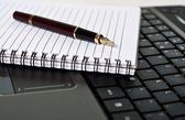 Pen, notepad and laptop on the desk — Stock Photo
