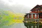 House by the lake in the mountains, Carpathians, Romania, Europe — Stock Photo