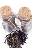 Tea leaves in transparent parisons with wooden spoon — Stock Photo