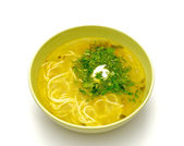 Bowl homemade chicken noodle soup with greens and sour cream — Stock Photo