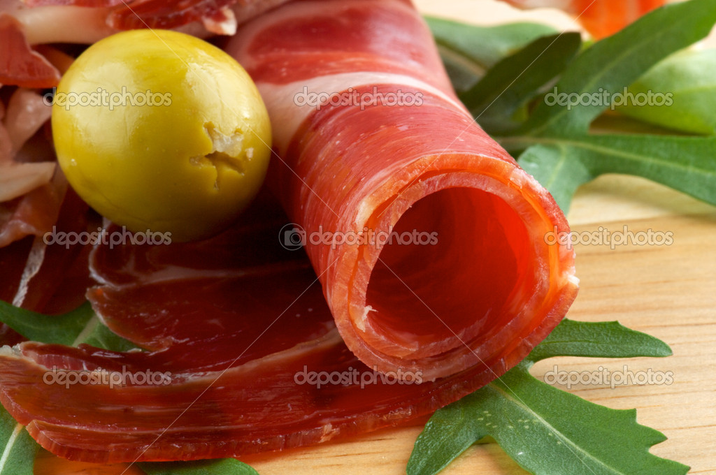 Slices of jamon and olives close up on wooden background  Stock Photo #9785376
