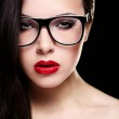 Fashion portrait of beautiful brunette girl model in glasses with birght makeup red lips. Clean skin. Isolated on black — Stock Photo