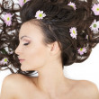 Stock Photo: Pretty beautiful girl lying with bright flowers in her hair bright makeup
