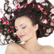 Stock Photo: Pretty beautiful girl lying with bright red flowers in her hair bright make