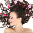 Pretty beautiful girl lying with bright red flowers in her hair bright make — Stock Photo