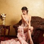 Beautiful bride in unusual wedding dress in the interior sitting in armchai — Stock Photo
