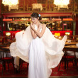 Beautiful bride in flying wedding dress in the restaurant — Stock Photo