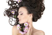 Pretty beautiful girl lying with bright flowers in her hair bright makeup i — Stock Photo