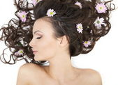 Pretty beautiful girl lying with bright flowers in her hair bright makeup — Stock Photo