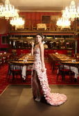 Beautiful bride in unusual wedding dress in the restaurant with cup of win — Stock Photo