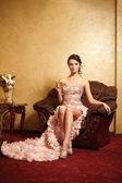 Schöne braut in ungewöhnliche hochzeitskleid in den innenraum sitzt in armchai — Stockfoto