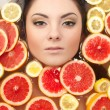 Close up portrait of smiling woman with many juicy citrus fruit lemon grape — Stock Photo