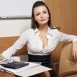 Beautiful business woman thinking about something sitting at the desk in t — Stock Photo