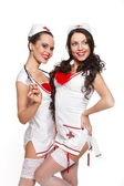 Two sexy beautiful smiling female brunette doctors in red lingerie white st — Stock Photo