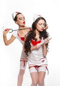 Two sexy beautiful female brunette doctors in red lingerie white stocking — Stock Photo