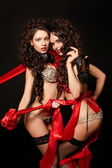 Fashion portrait of two sexy brunette girls in light lingerie with long cur — Stock Photo