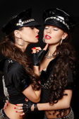 Two sexy beautiful brunette semi nude police women with long curly hair wi — Stock Photo