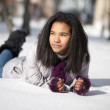 Beautiful american black female lying in the snow outdoors — Stock Photo