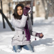 Beautiful smiling american black female sitting in the snow outdoors playing with snow — Stock Photo #9616766