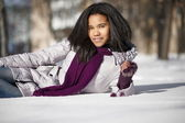 Beautiful smiling american black female lying in the snow outdoors — Foto de Stock