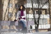 Prachtige Amerikaanse zwarte vrouw in de straat buiten winter zittend op een bankje — Stockfoto