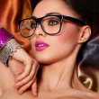 Fashion portrait of beautiful brunette girl model in glasses with birght makeup pink lips and unusual haistyle bright colorful background with accessory — Stock Photo #9653295