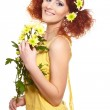Portrait of beautiful smiling redhead ginger woman in yellow cloth with yellow pink colorful flowers in hair isolated on white holding flowers — Stock Photo