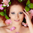 Closeup portrait of beautiful smiling redhead ginger woman face with colorful flowers in hair in porofile — Stock Photo