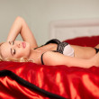 Royalty-Free Stock Photo: Portrait of beautiful sexy girl lying on the bed in lingerie with bright makeup and hairstyle