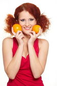Portrait of beautiful smiling redhead ginger woman in red cloth isolated on white with oranges — Stock Photo