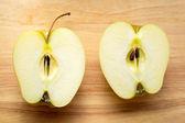 Dwie połówki jabłka na drewnianym stołem — Zdjęcie stockowe