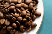 Coffee beans on white saucer — Stock Photo