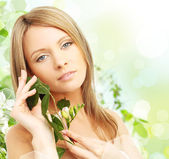Beautiful young woman with spring blossom — Stock Photo