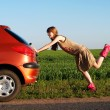 Pushing a car — Stockfoto