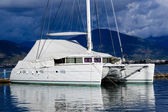 Sailing catamaran morred. Heavy sky background and reflections on water vivid image. — 图库照片