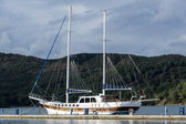 Old style big two mast sailing vessel moored. Mountain background. — Stock Photo
