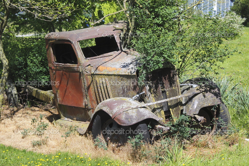 Mother Nature slowly takes back an old, discarded vehicle from the 1920s.   Stock Photo #10624093