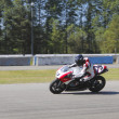 Motorcyclist races down track - Foto Stock
