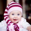 Cute happy baby in striped hat with bobble — Stock Photo #8043374