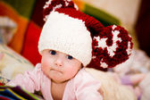 Cute little baby in wool hat with big pompoms — Stock Photo