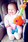 Baby girl smile in carseat — Stock Photo