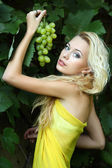 Portrait of a beautiful young blonde with a bunch of grapes — Stock Photo