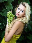 Retrato de una bella joven rubia con un racimo de uvas — Foto de Stock