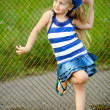 Portrait of a little girl who poses near the grid — Stock Photo #9411452