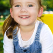 Portrait of smiling cute little girl outdoors — Stock Photo